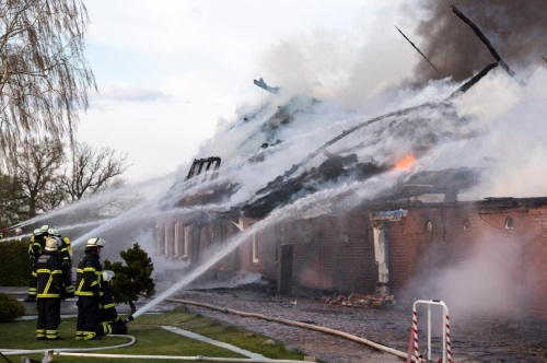 Firefighters put out the remaining fire at a thatched cottage in Hamburg, Germany, April 18, 2015. The fire broke out in the historic district of Neuengamme and consumed the house completely. (EPA/DANIEL BOCKWOLDT)
