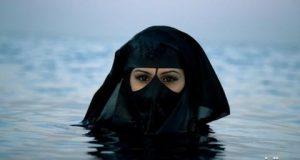 شنای زن سعودی در ساحل با روبنده +عکس